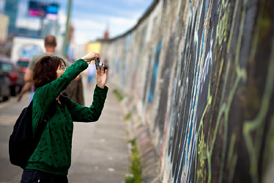 Tourist taking a photo of Berlin Wall